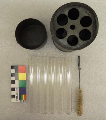 Cylindrical metal container with six test tubes and wire brush
